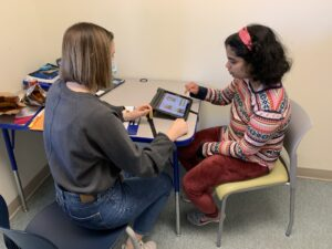 A girl in a pink striped sweater points to an iPad while seated in front of a teacher in a classroom.