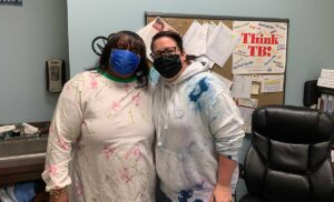 Two women in masks pose for a photo in a nurses office.
